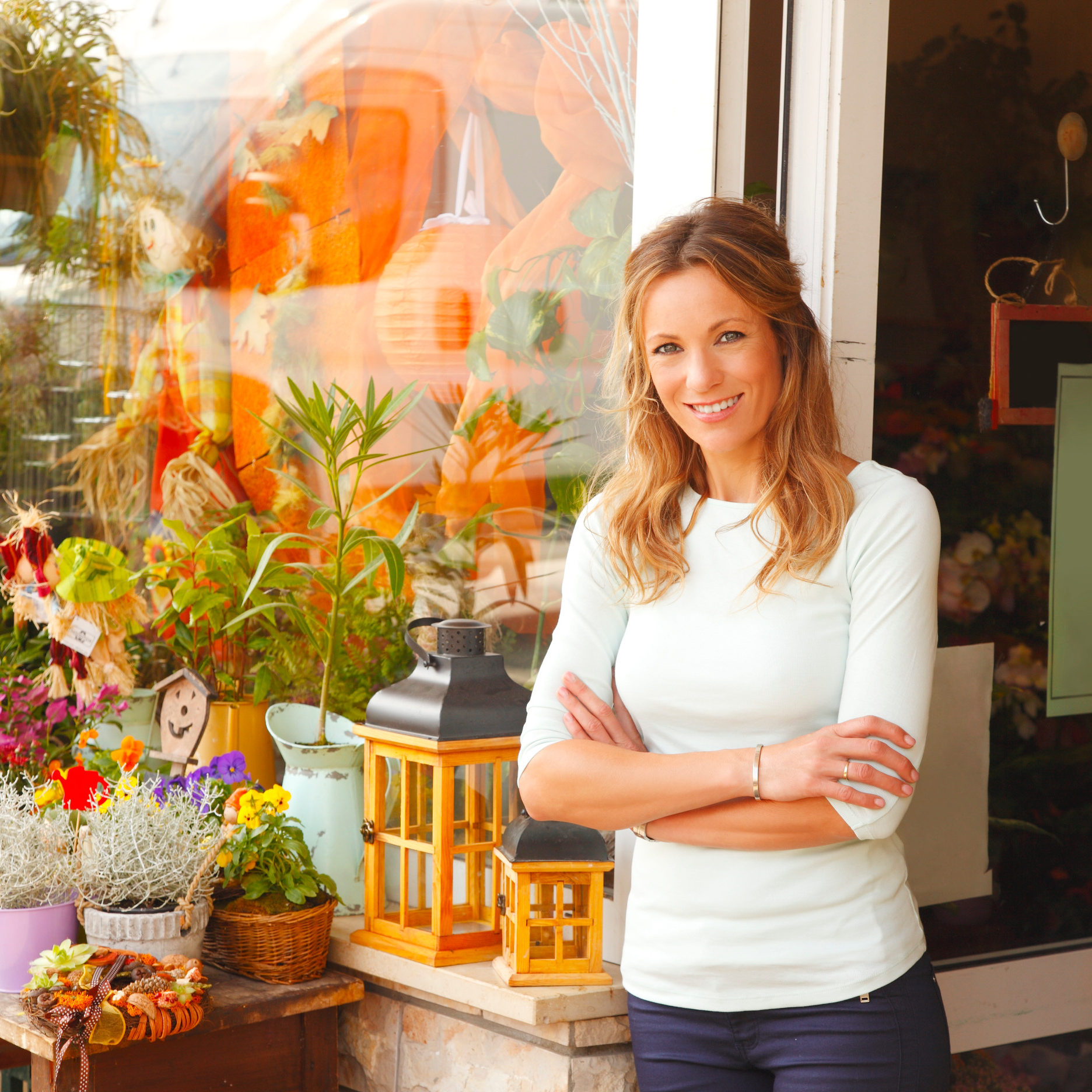Portrait of smiling florist standing in front of flower shop's facade. Small business.